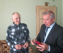 Глава района В.А. Домрачев вручает медаль ветерану Великой Отечественной войны И.Г. Царегородцеву.