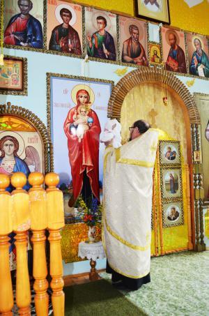 Батюшка подносит окрещенную к царским вратам